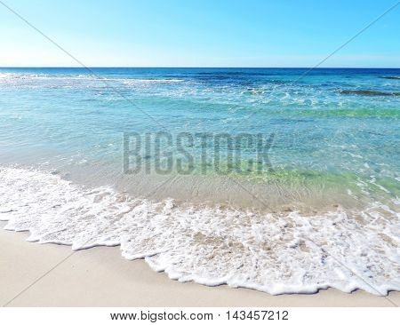 Tropical beach in the sun, beach background scene with clear blue sky and waves rolling on the beach.