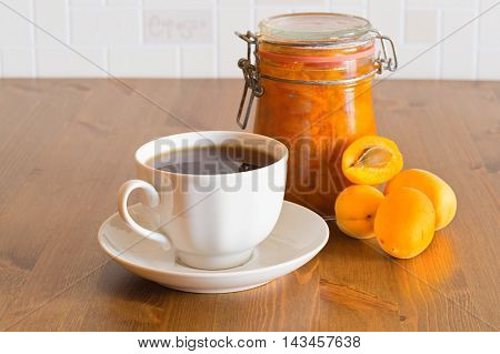 Homemade organic apricot jam in glass jar with apricots and tea on wooden table