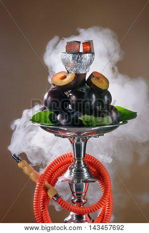 Smoking hookah with fruit tray on dark background