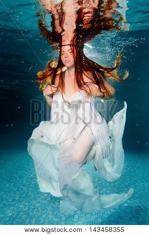 Young woman underwater with white textile floating