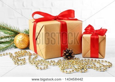 Gift boxes with Christmas tree branch and decor on brick wall background