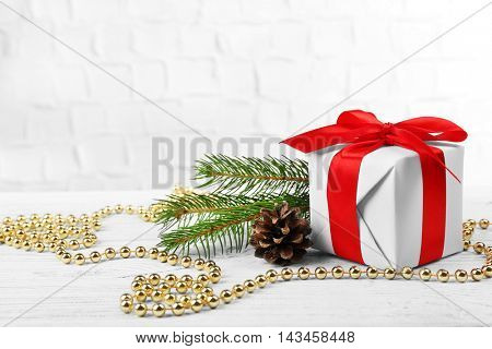Gift box with Christmas tree branch and decor on brick wall background
