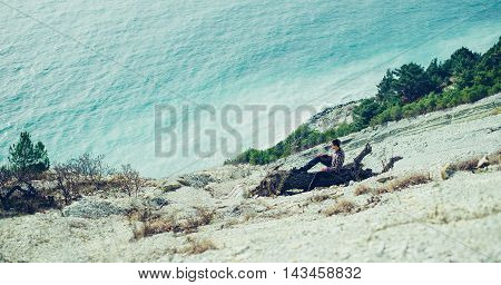 Young man resting on wooden snag on coast and enjoying view of sea