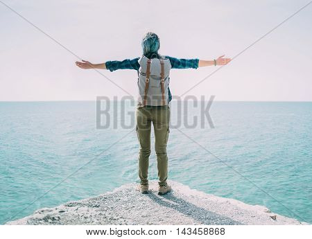 Happy explorer young woman standing with raised arms on edge of rock and enjoying view of sea in summer rear view