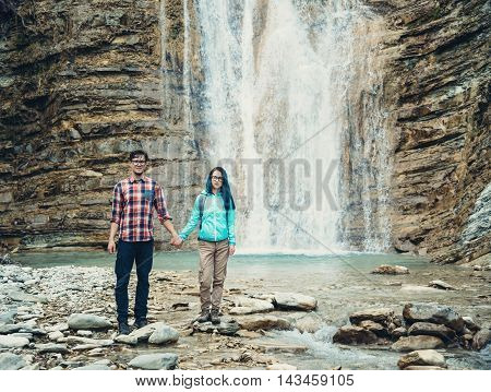 Explorer young couple standing on background of waterfall outdoor