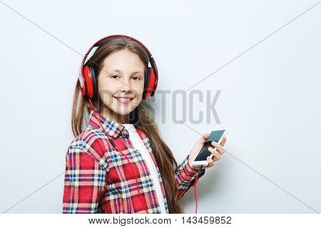 Portrait Of Young Girl With Headphones On Grey Background