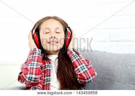Portrait Of Young Girl With Headphones On Grey Sofa