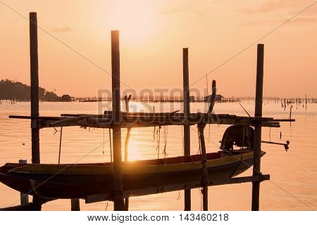 Long tail boat at beautiful sunset orange sky reflect with water lake at traditional folk fishing village in south Thailand.