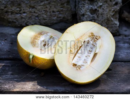 Ripe cut melon on a wooden table and a stone background