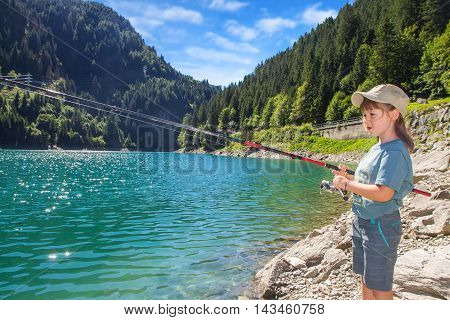 young girl fishing in a lake in the mountains