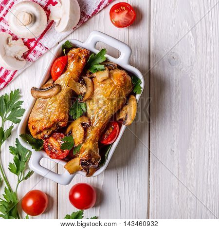 Chicken legs fried with mushrooms and tomatoes top view.
