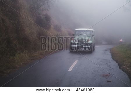 Adventurous off road drive on the downhill road with fog hazy environmentand wet road at dawn