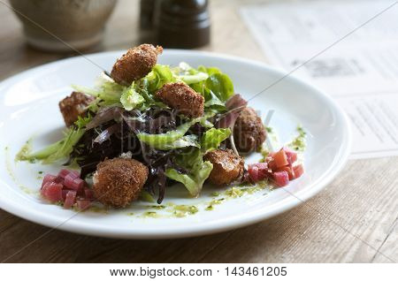 Fried cheese and rhubarb salad on a white plate