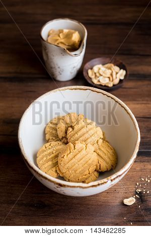 Homemade oatmeal cookies with peanut butter and nuts in a bowl on a wooden dark brown table, selective focus