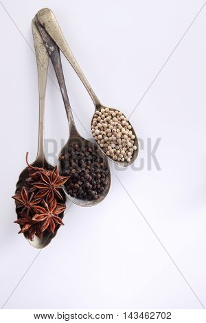 few spoons with spices on the white background