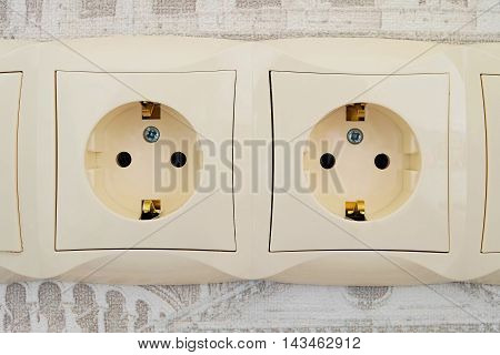 Detail of an electric socket block with two connection points. Interlocked electrical outlet on the wall.