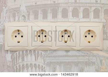 Electric sockets block of four connection points. Interlocked electrical outlets on the wall.