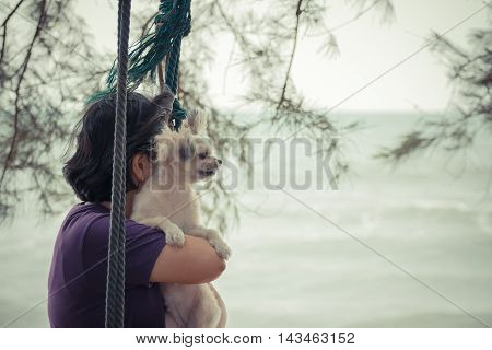 Asia Woman And Her Dog Posing On Swing At Beach With Blue Sea And Sky