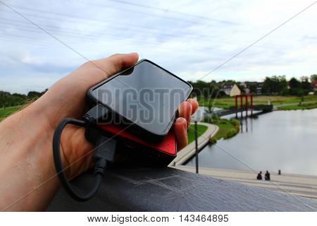 A black smartphone on a red powerbank lying on a fence in a residential district with a pond and lots of green vegetation