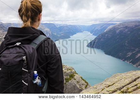 Dramatic clouds and female tourists hiking at a high mountain in a fjord. Preikestolen also known by the English translations of Preacher's Pulpit or Pulpit Rock. Cliff in Forsand Ryfylke, Norway.