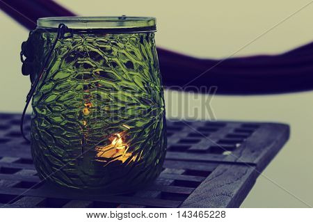 Dark green lantern on teak coffee table in front of hammock on balchony with glass sidings.