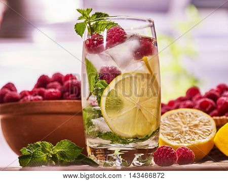 Alcohol drink. On wooden boards alcohol glass with straw and ice cubes. Drink two hundred ninety cocktail raspberry mojito with lime and mint leaf. Country life. Outdoor country . Light background.