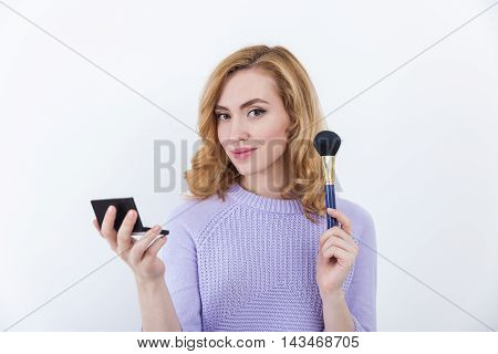Sexy lady with wavy hair in purple sweater holding powder and brush. Concept of good make-up artist in cinematography