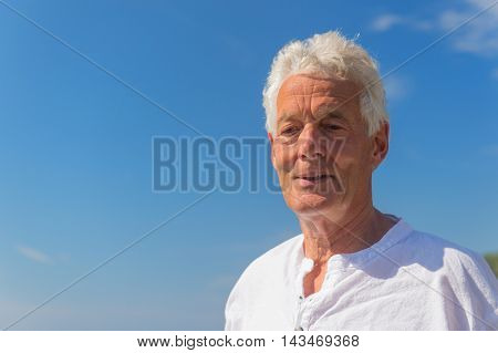 Portrait senior man against blue sky