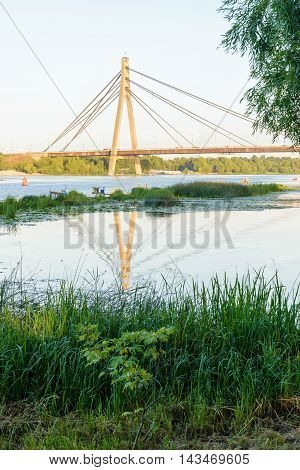 A view of the Moskovsky bridge over the Dnieper river in Kiev Ukraine during a blue summer evening
