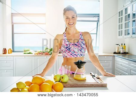 Beautiful vivacious woman preparing fruit juice from fresh ingredients in her kitchen in a healthy diet and lifestyle concept