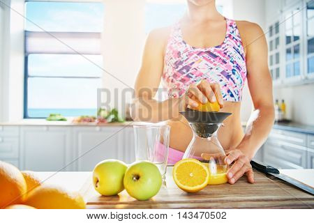 Cropped low angle view across the counter of a shapely fit healthy woman making fresh juice from apples and oranges using a manual blender with high key copy space on a window
