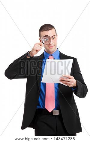 Shocked man analyzing a bill with a magnify lens