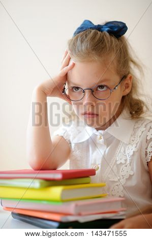 Cute little schoolgirl pondered. Girl in glasses sits leaning on a stack of books. She had a serious expression on his face.