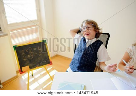 Naughty little schoolboy in glasses cheerfully laughs. This elementary school student. Near to a school desk of the child there is a small blackboard. Back to school.