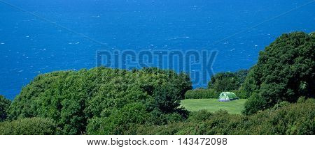 Lonely tourist tent in the clearing. North Coast of Devon County. Exmoor National Park. England