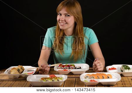 attractive smiling woman sitting at the table with rolls