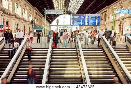 BUDAPEST, HUNGARY - MAY 29, 2016: Rushing people inside the structure of Keleti railway station with trains on platform on 29 May, 2016. International railway terminal in Budapest was constructed in 1884