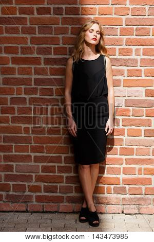 Beautiful blond woman standing at full height half body in shadows and half body in sun