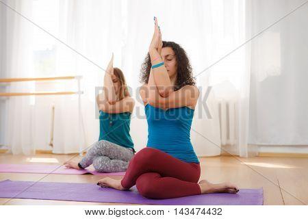 Two beautiful european young women practicing yoga or pilates in gym, closeup portrait