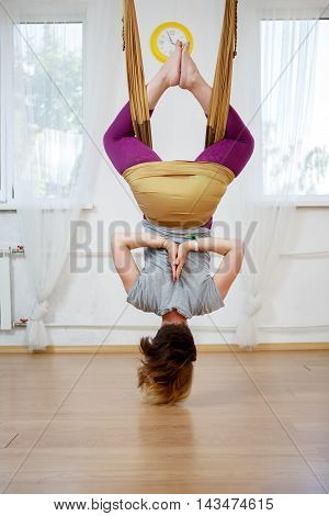 Back view of young woman doing yoga pose in hammock of antigravity yoga in class