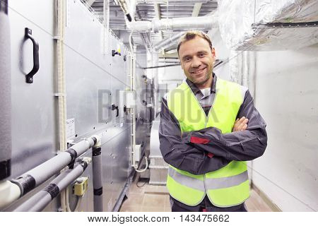 Worker in electrical switchgear room of CNC plant