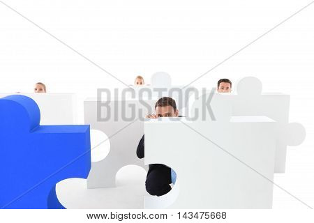 Group of business people hiding behind jigsaw puzzle isolated on white background