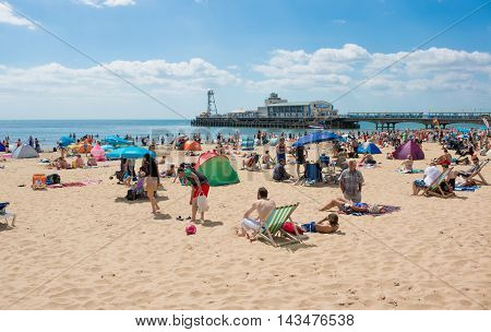 BOURNEMOUTH, UK - 09 AUGUST 2016: General view on the beach in Bournemouth with pier amusements in the background, in a sunny summer day