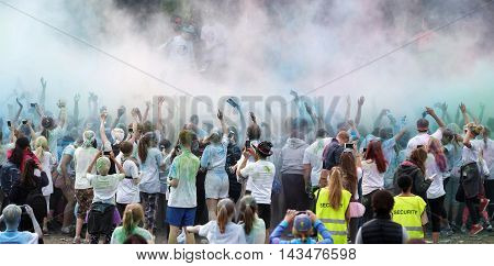 STOCKHOLM SWEDEN - MAY 22 2016: Happy audience with arms in the air and color powder in the air in the Color Run Event in Sweden May 22 2016