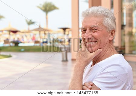 happy senior man on a walk in the park in summer