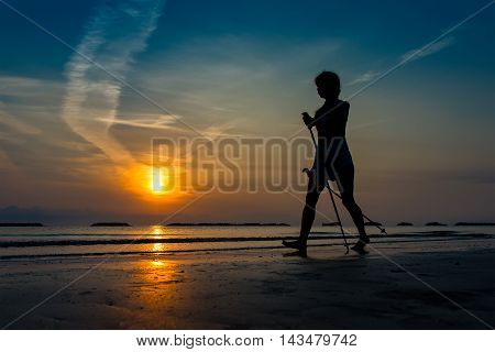 Woman Practicing Nordic Walking In The Beach At Sunrise In Late Summer