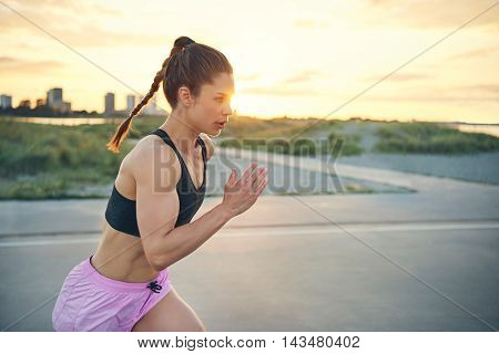 Fit young woman practising her sprinting technique training on a rural road at sunrise running across the front of the lens