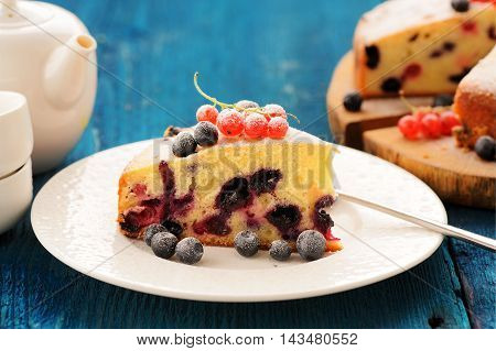 Homemade yummy cake with blueberries and red currants closeup