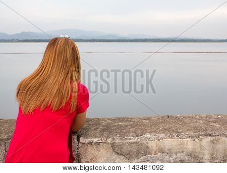 woman red T-shirt stand and look dam view