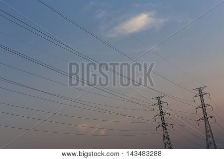 high voltage pole of transmission lines at twilight sunset.
